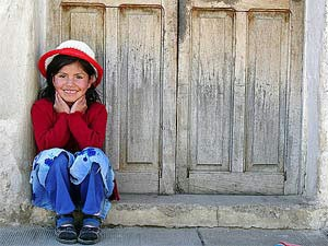 Local Bolivian child sitting in a doorway smiling