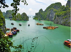 View across Halong Bay with emerald green water and boats scattered across the water