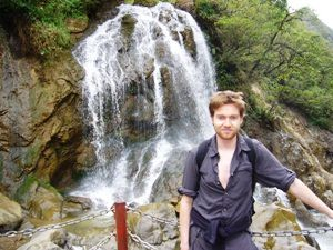 Man standing in front of a waterfall
