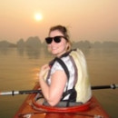 Lady turning to smile at the camera while kayaking at sunset in Halong Bay in Vietnam