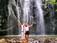 Women standing in front of a waterfall smiling in Cambodia