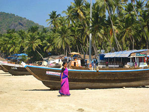 India local woman walking by boats on beach in Goa India