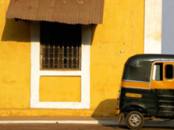 India parked tuk tuk against yellow wall
