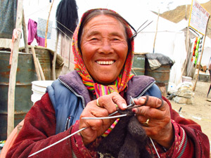Local woman knitting in colourful clothing in Leh India