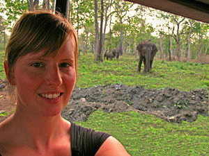 Woman with elephant in the trees in the background in India