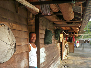 Local tribesman smiling from the doorway of his home