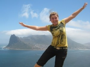 woman jumping in front of mountain in south africa