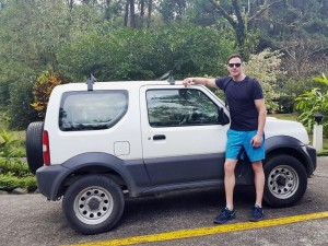 Young man standing in front of white 4x4 in costa rica
