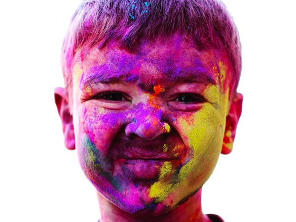 Young boy at the Holi Paint Festival in India, covered in multicoloured paint