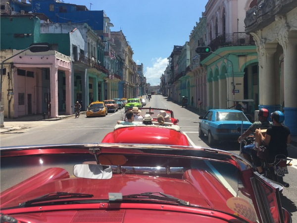 Row of open top classic cars driving through the street