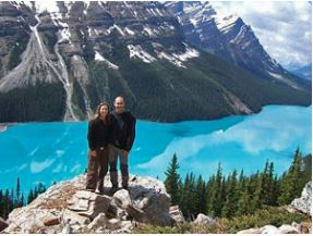 Couple standing on rock with landscape view of green Canada lake and mountains in background