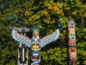Colourful totem poles in front of trees