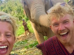 laughing man and woman with elephant in background