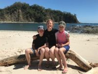 family sitting on a tree trunk on the beach with sea in background